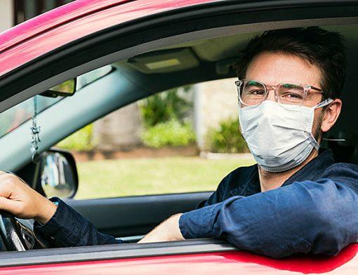 motorista ao volante usando mascara
