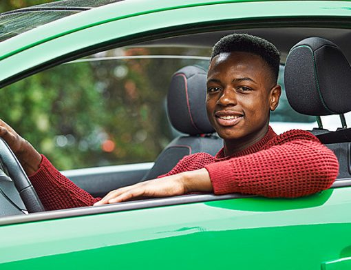 homem jovem ao volante de um veiculo parado