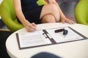 mulher sentada assinando contrato